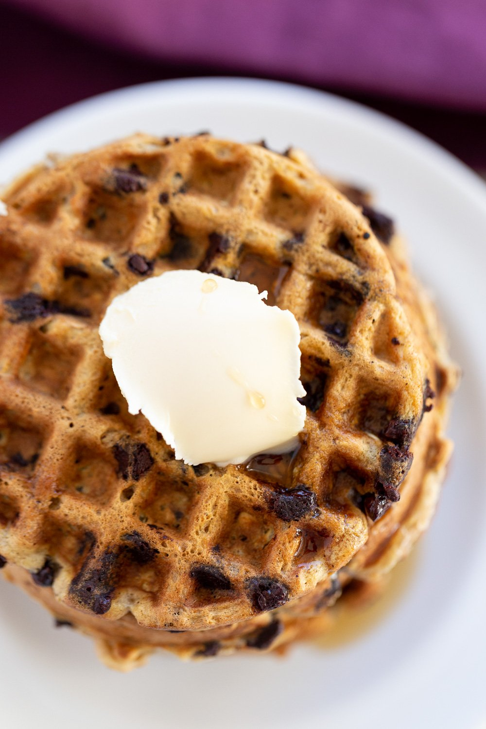 overhead shot of a stack of healthy vegan oatmeal chocolate chip waffles topped with ice cream