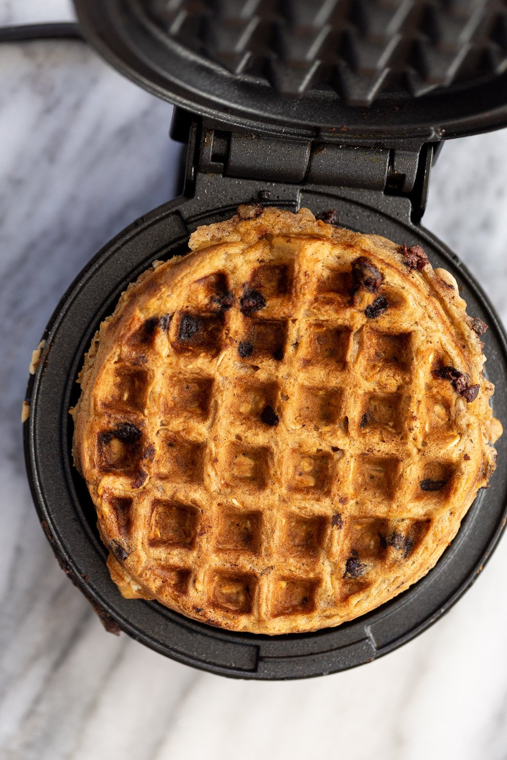 a vegan oatmeal chocolate chip waffle being baked in a black iron waffle maker