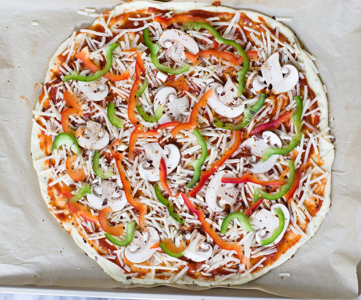 overhead shot of unbaked vegan pizza on a baking sheet topped with vegetables and vegan cheese shreds