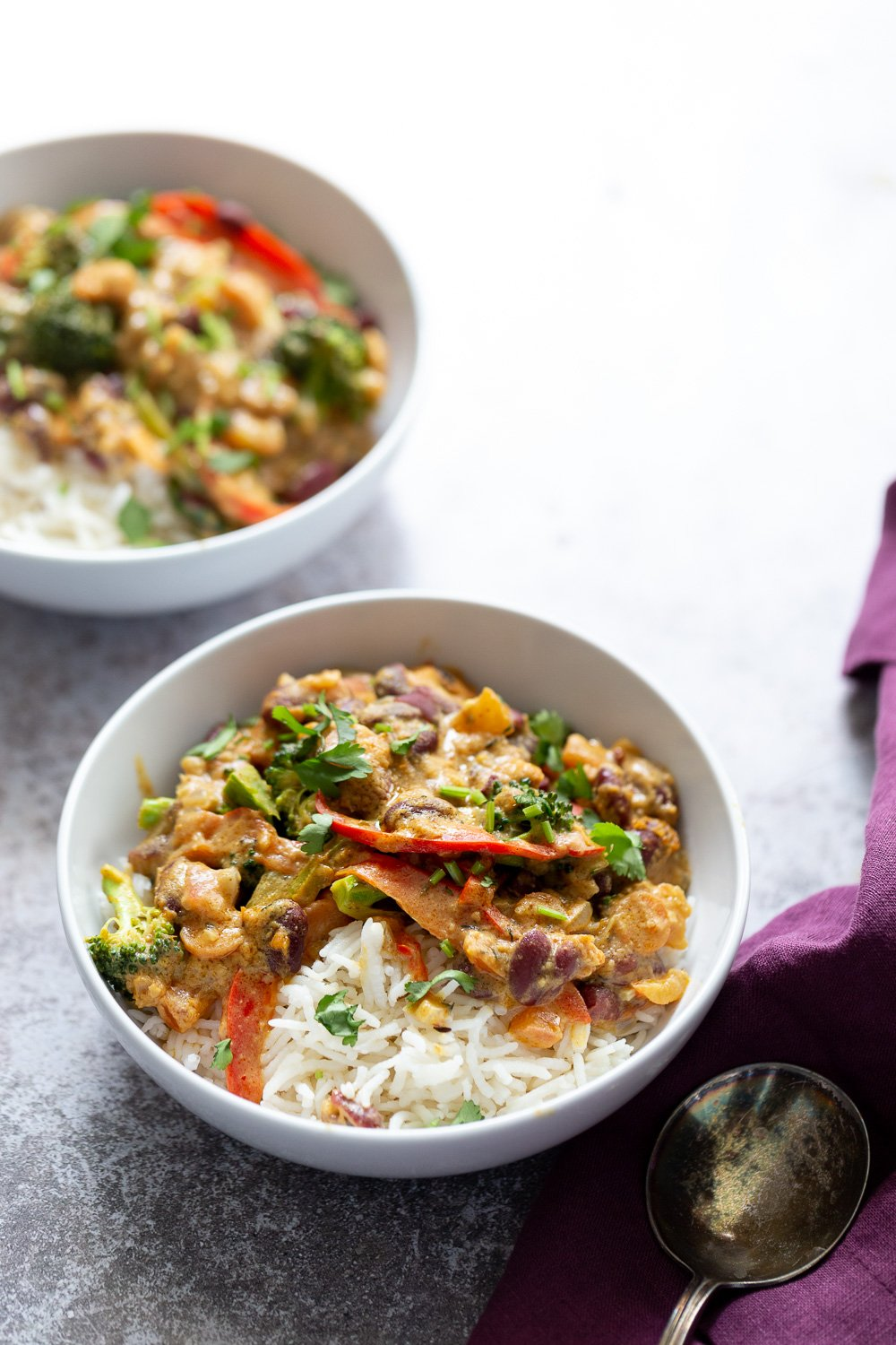 two bowls of vegan creamy coconut mild and kidney bean Peanut Stew served with rice