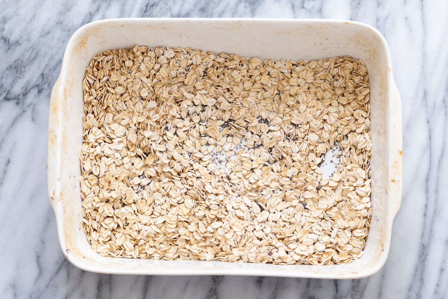 overhead shot of a casserole dish filled with rolled oats and chia seeds