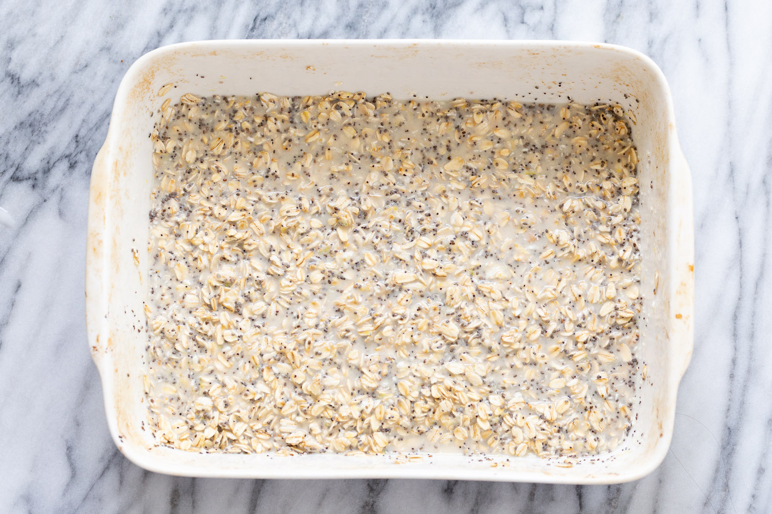 rolled oats and chia seeds being mixed with plant based milk to make baked oatmeal