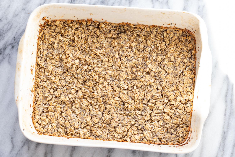overhead shot of freshly baked vegan baked poppyseed and lemon oatmeal in a white casserole dish