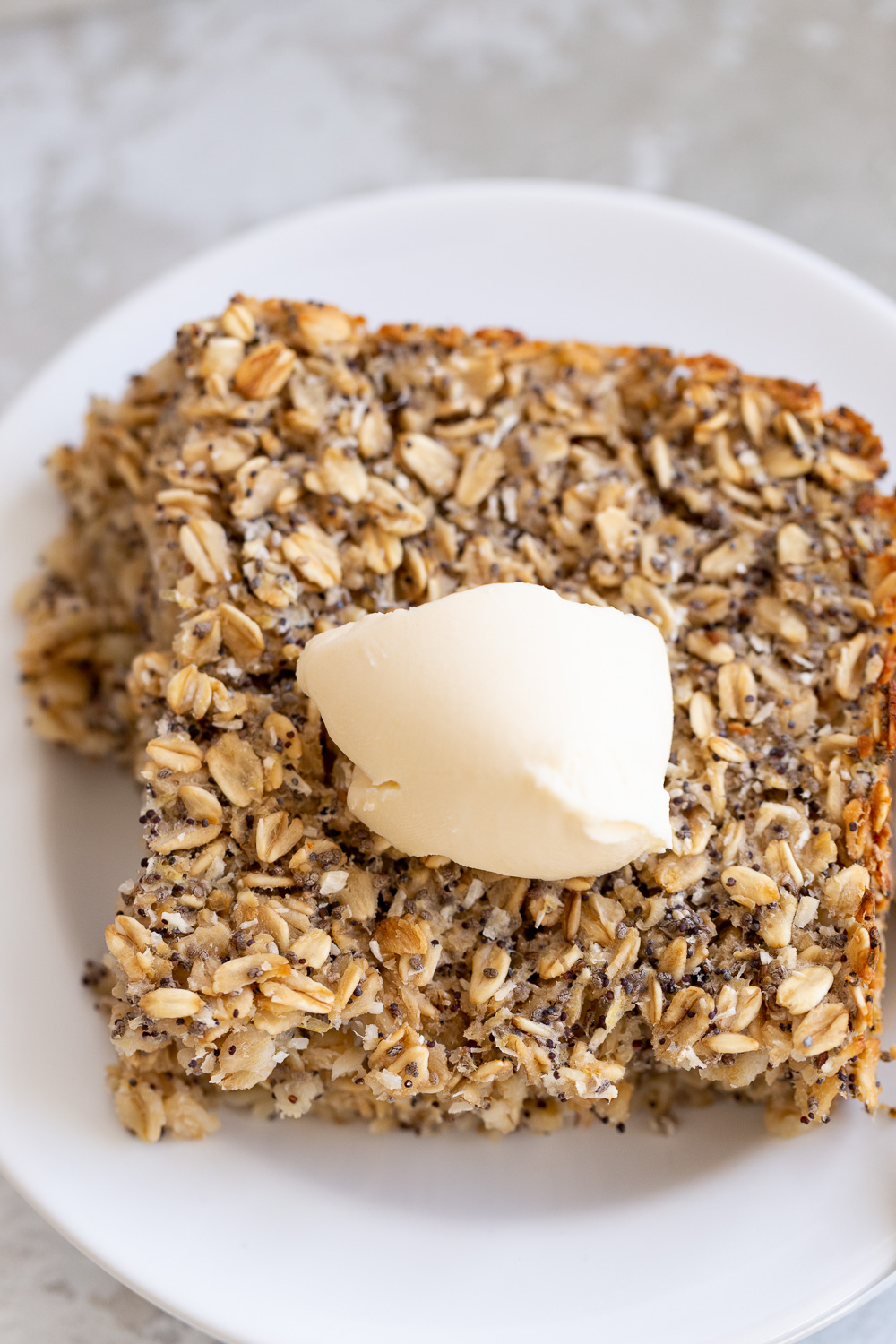 overhead shot of a square of healthy vegan baked poppyseed lemon oatmeal topped with coconut whipped cream