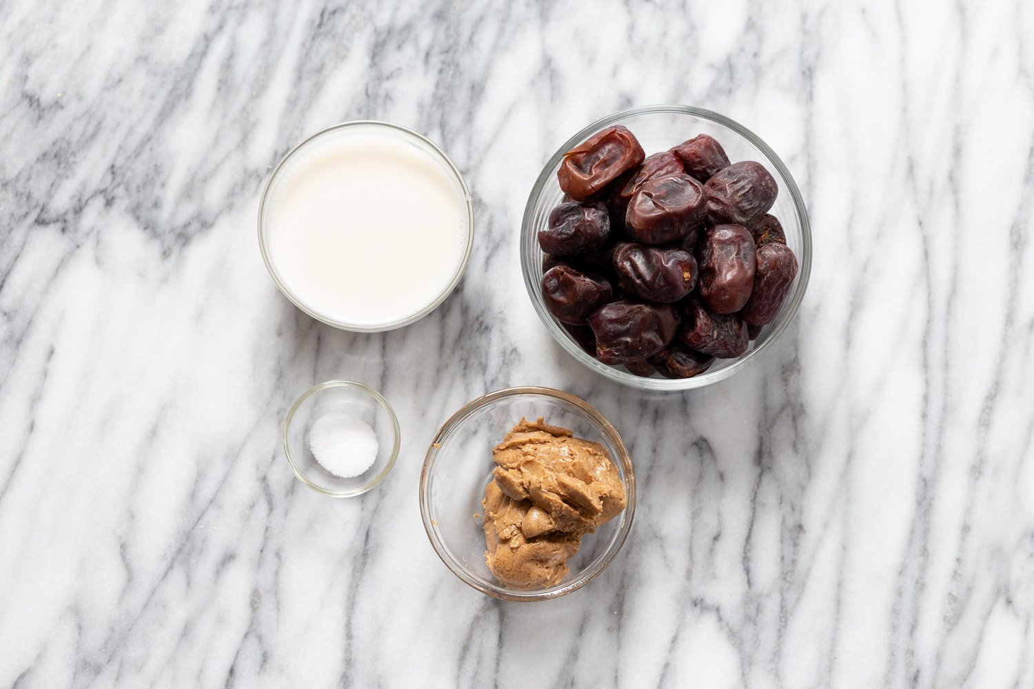 small glass dishes with plant based milk, dates, nut butter and salt on a kitchen counter