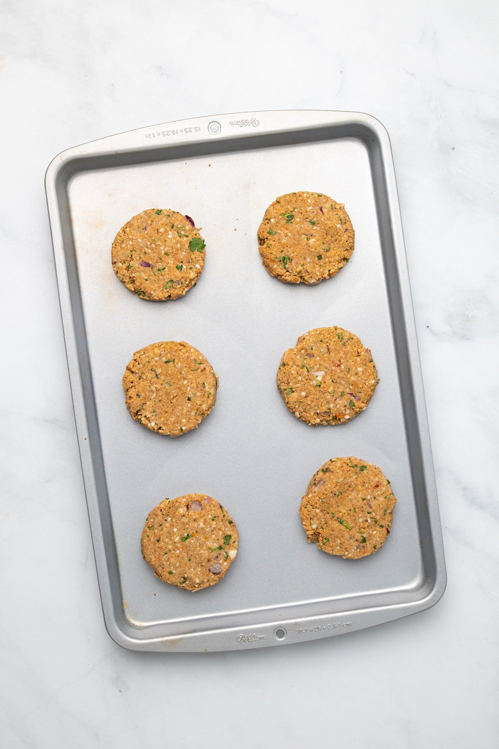 overhead shot of vegan chickpea burger patties lined up on a cookie sheet