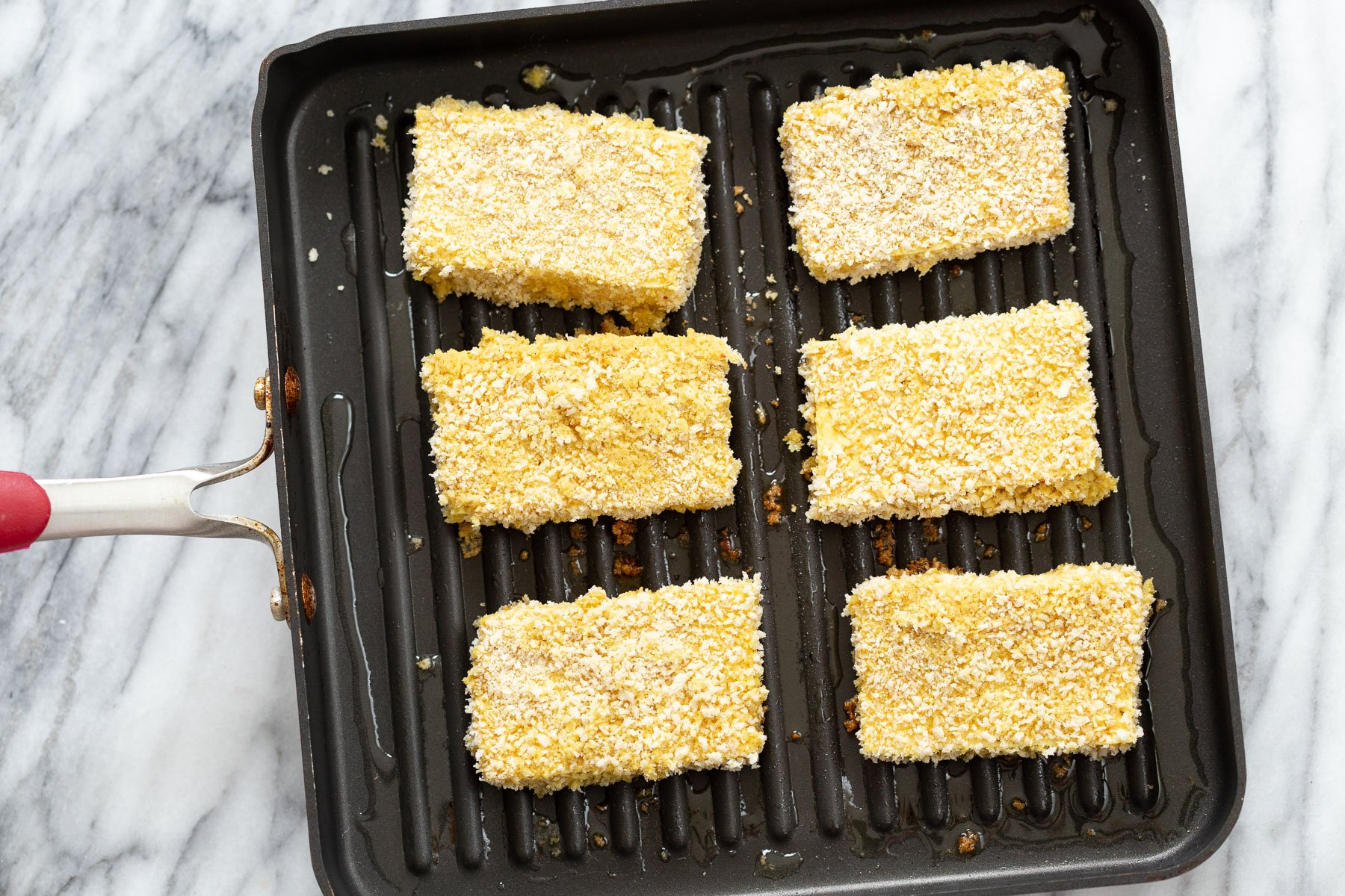 breaded tofu slices being fried in a pan