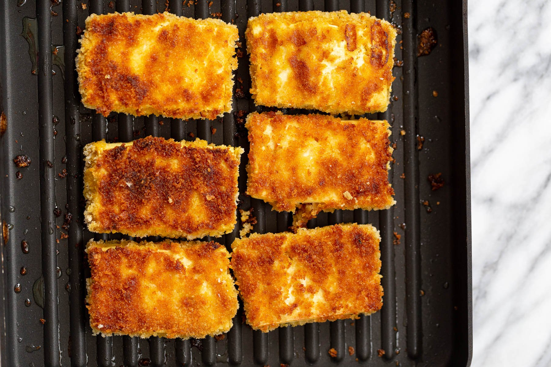 breaded tofu sliced being fried in a grilling pan