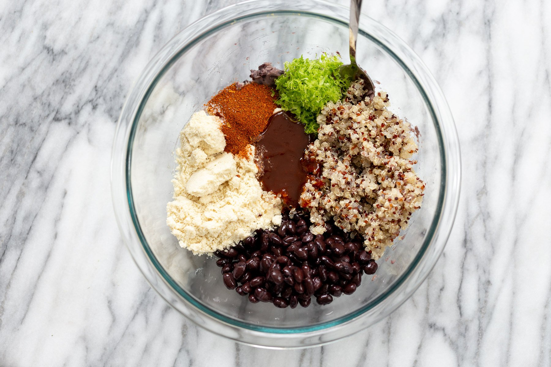 ingredients for making black bean quinoa patties gathered in a glass bowl