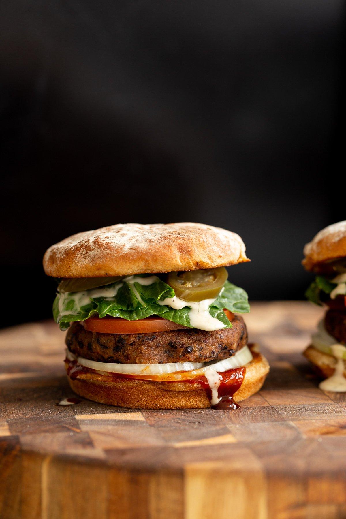 vista lateral de um hambúrguer vegano de quinoa de feijão preto coberto com jalapenos em conserva e molho do rancho