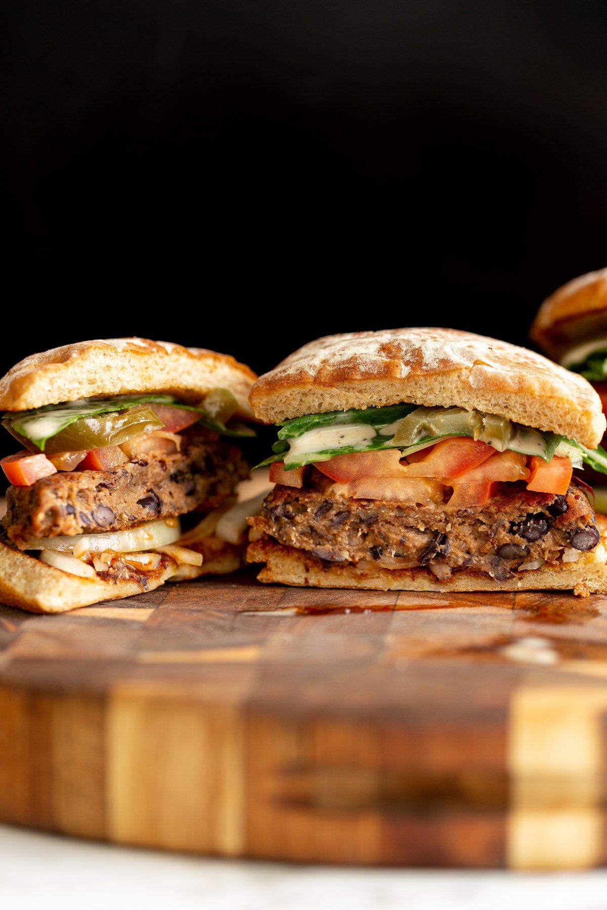 um hambúrguer vegano de quinoa de feijão preto, coberto com fatias de tomate e regado com molho de rancho