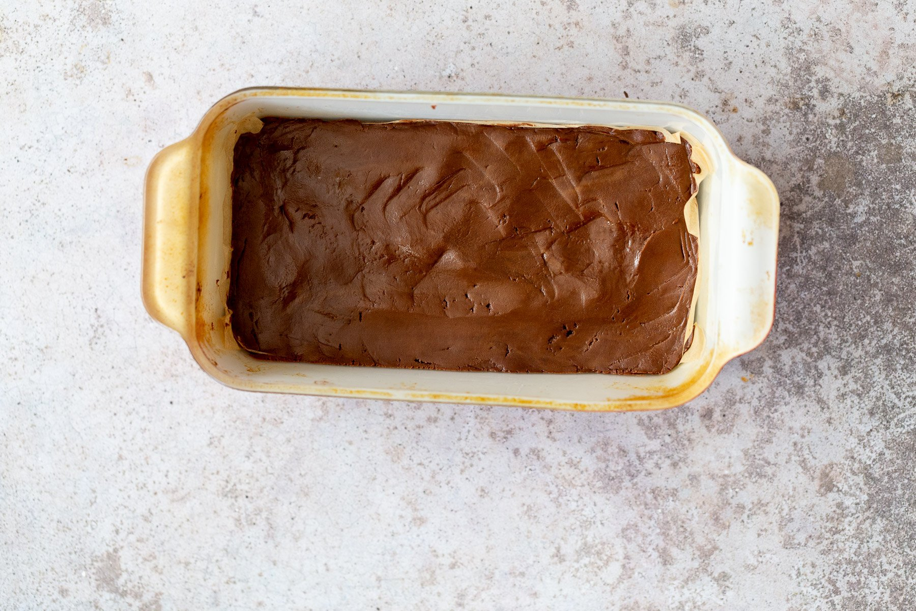 vegan chocolate fudge in a white loaf pan ready to be chilled