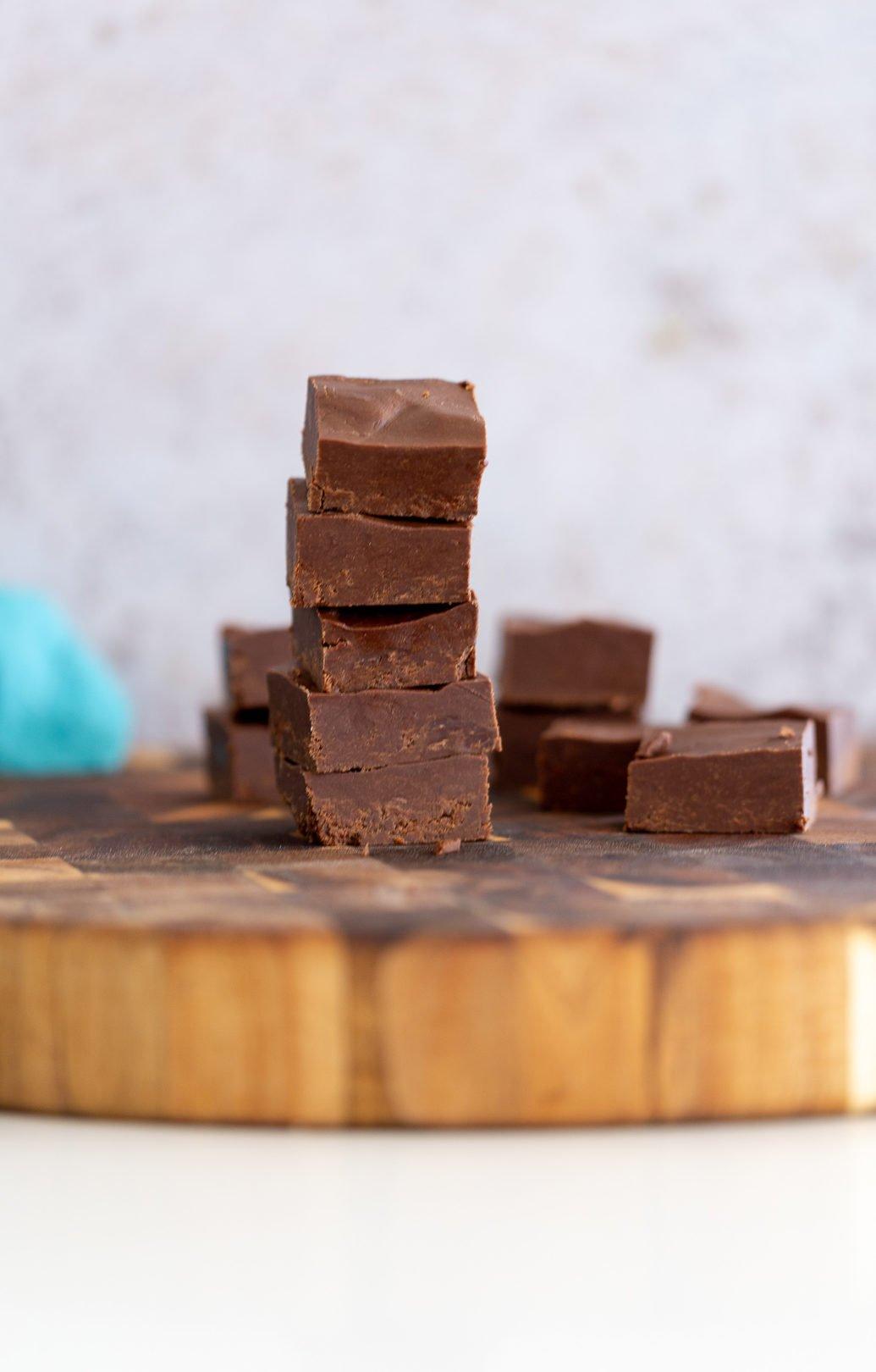 uma pilha de calda de chocolate vegana fácil e saudável em uma placa de madeira rústica