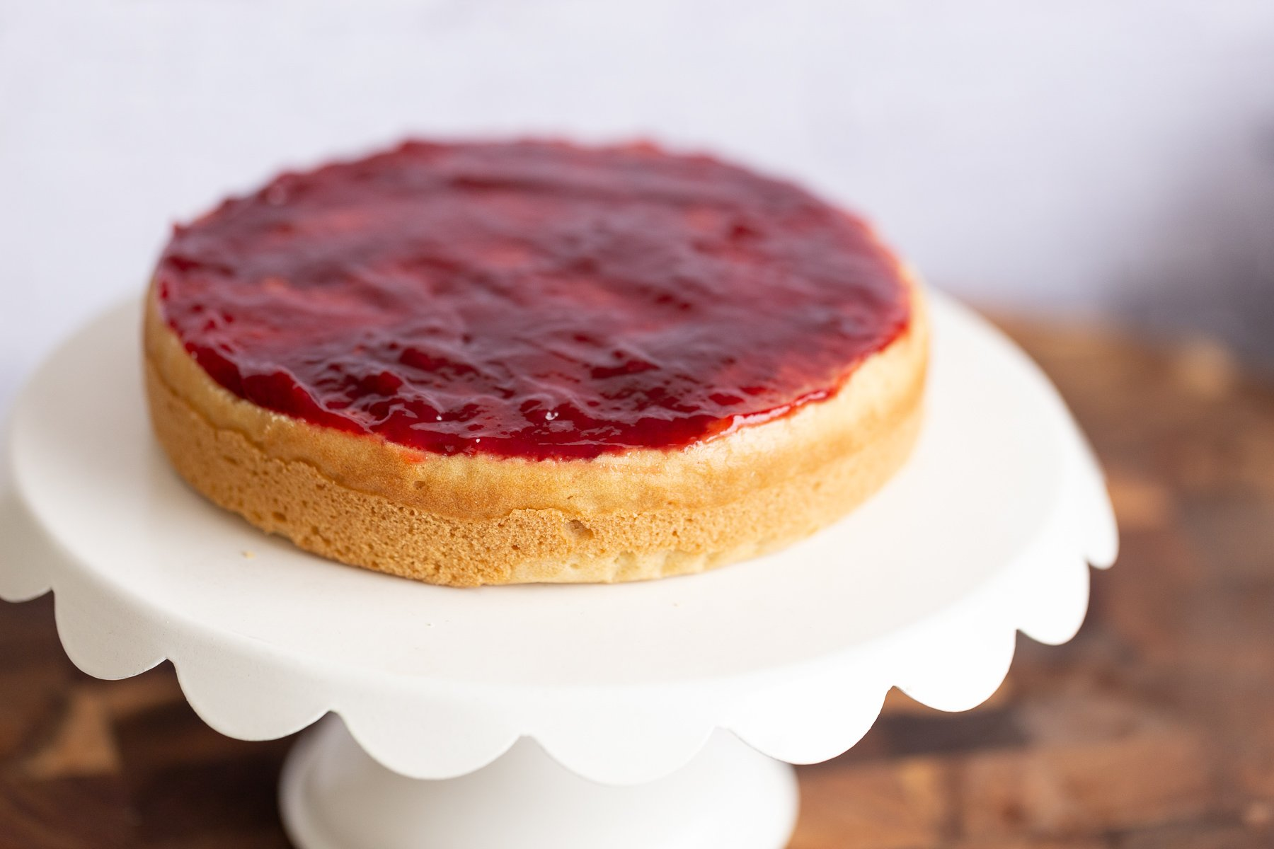 vegan sponge cake topped with raspberry jam