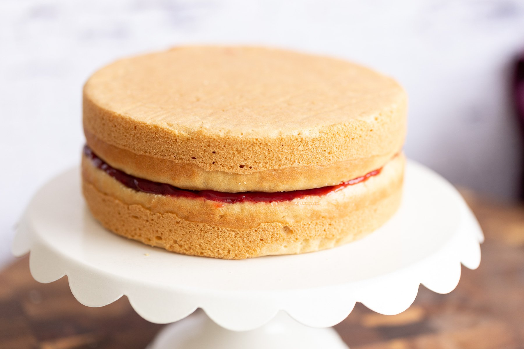 assembled vegan white cake filled with raspberry jam on a cake stand