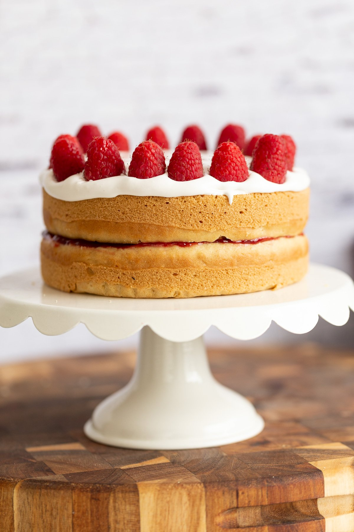 a vegan white cake topped with coconut whip and raspberries on a white cake stand