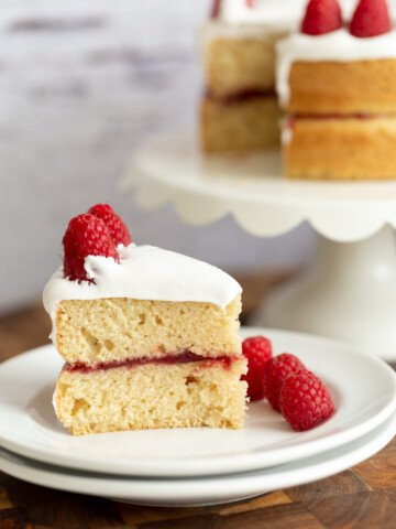 side view of a slice of vegan white cake filled with raspberry jam