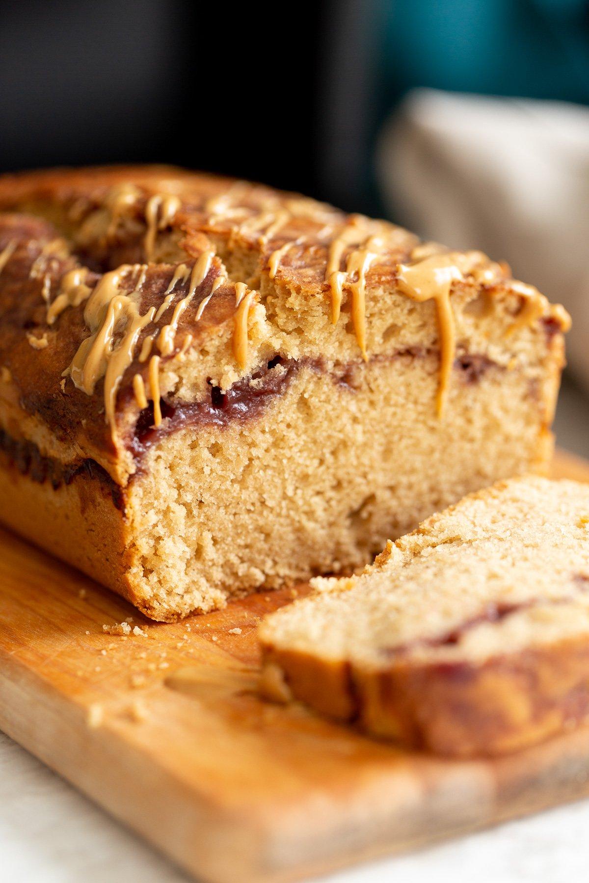 close up de um bolo de pão de pb e j vegan fatiado regado com manteiga de amendoim em uma tábua