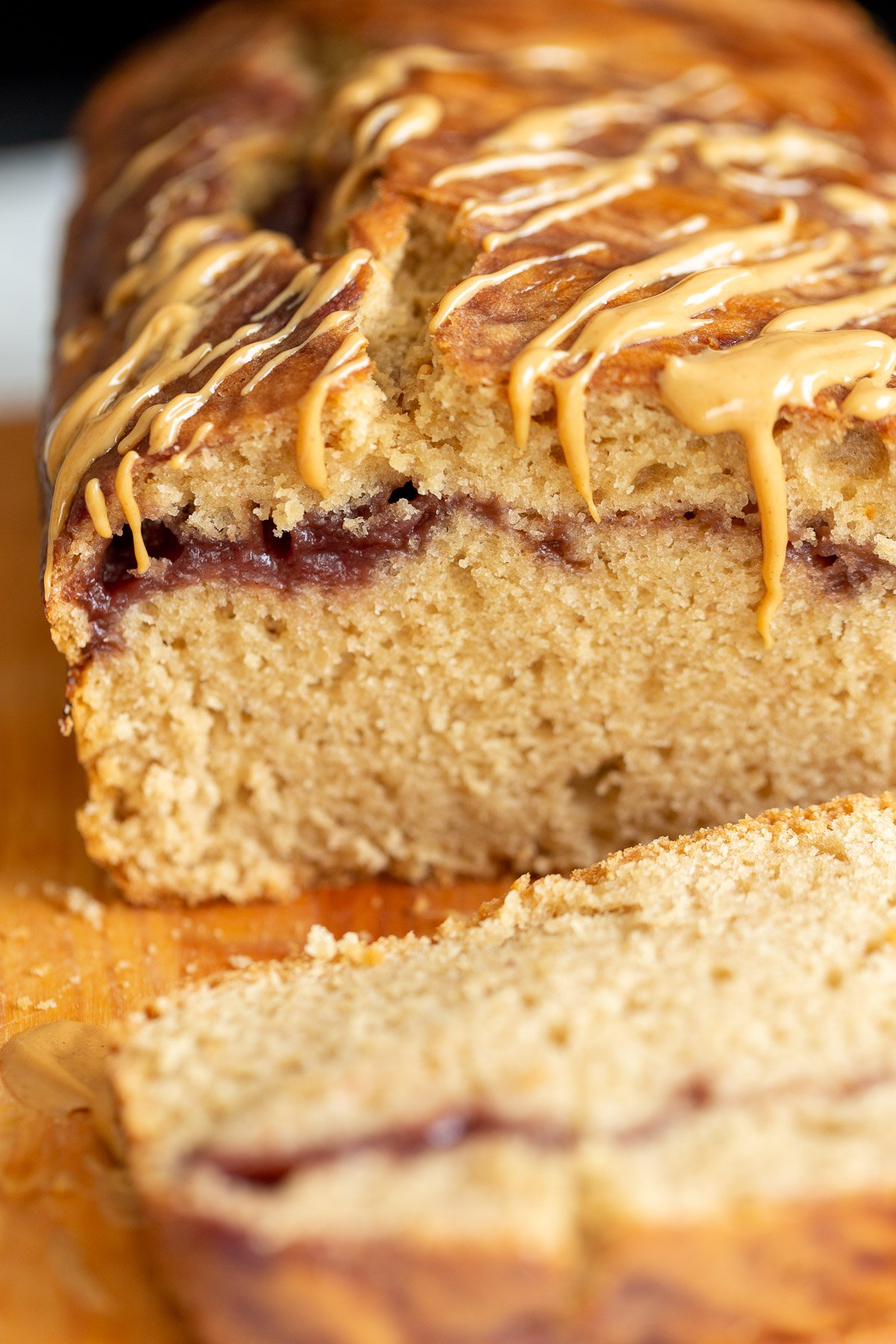close up of a sliced loaf of vegan peanut butter and jelly cake with jam swirl