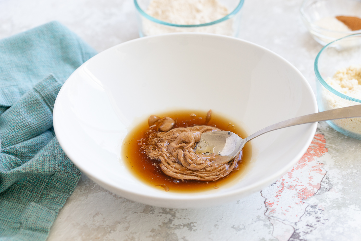 maple syrup and nut butter being stirred together in a small bowl