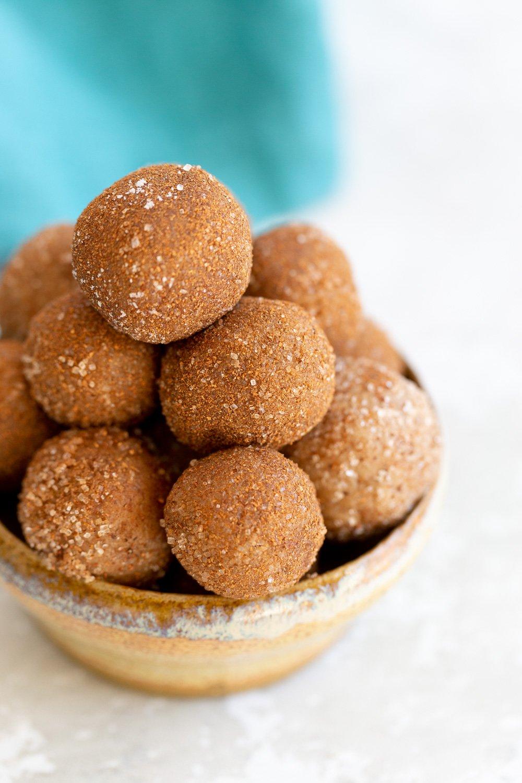 Vegan Snickerdoodle Snack Bites enrolado em açúcar canela em uma pequena tigela de barro