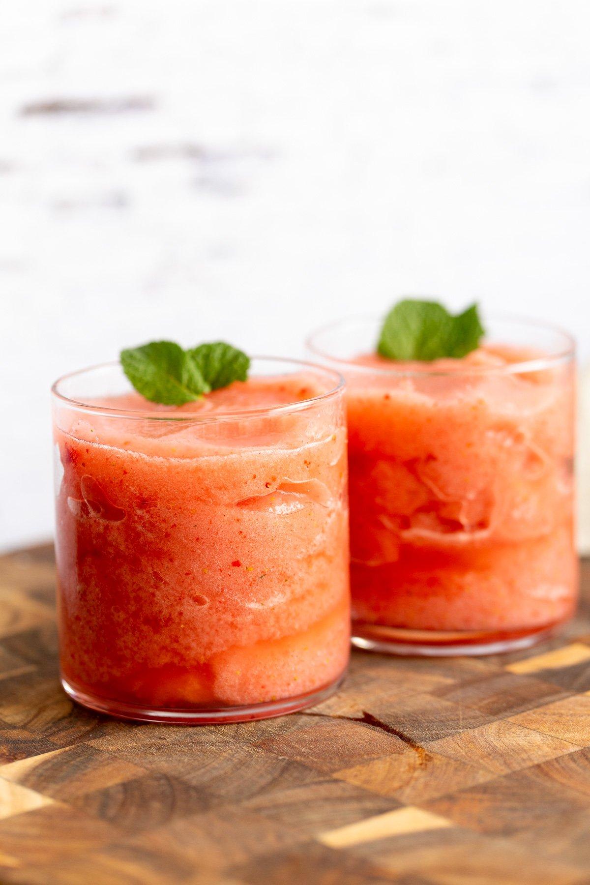 two glasses with homemade vegan strawberry lemonade slushies