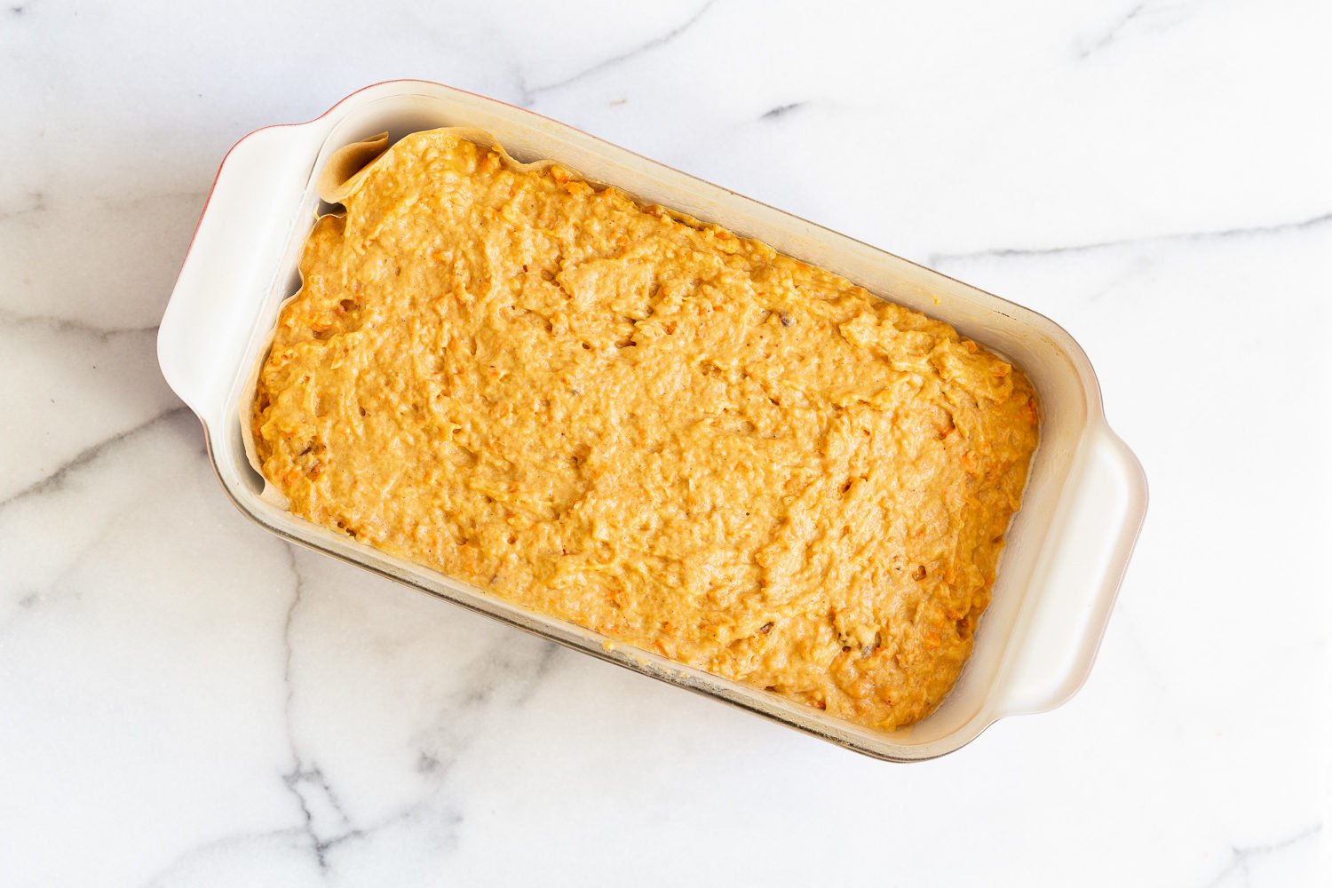 vegan pumpkin carrot cake batter in a loaf pan ready for baking