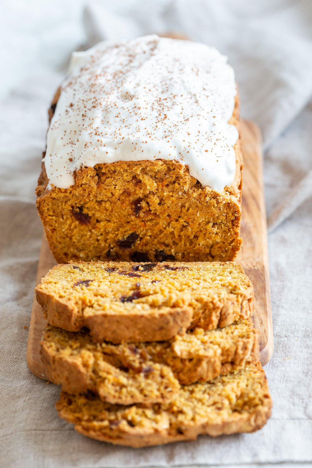 a sliced loaf of vegan pumpkin carrot bread on a wooden cutting board