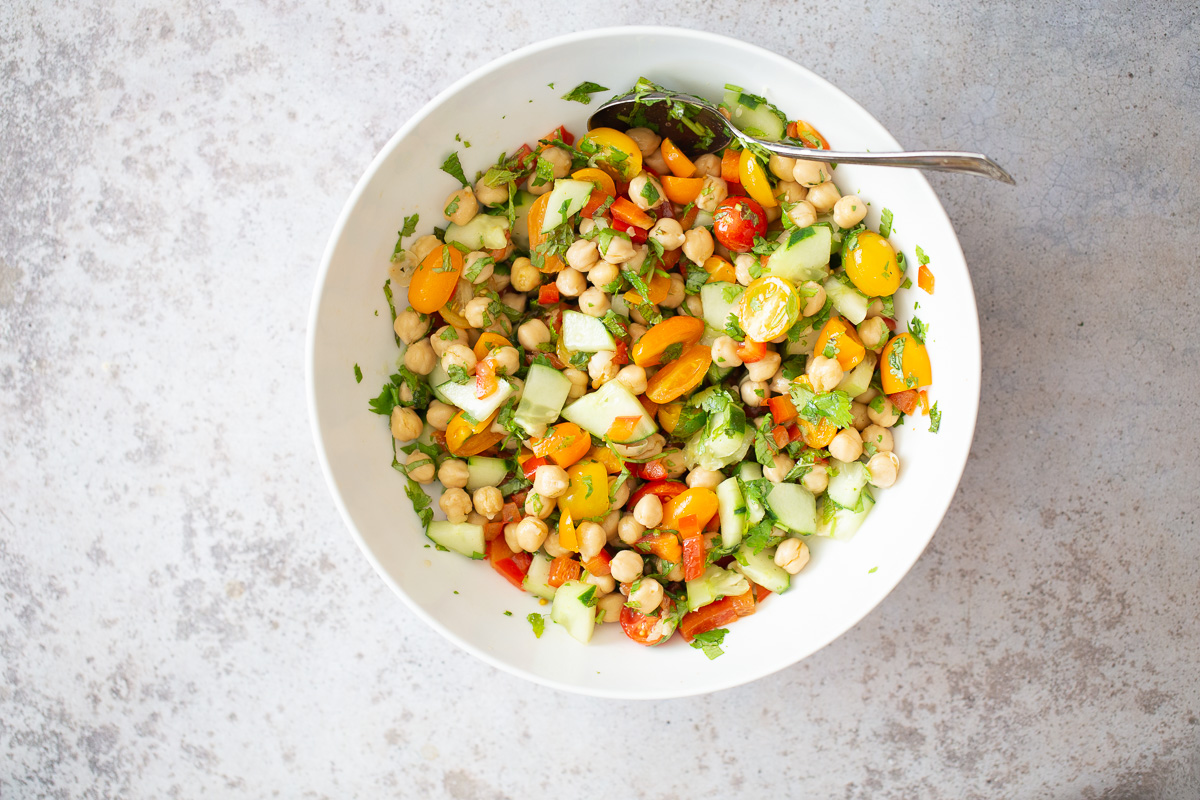 balela chickpea salad ingredients being tossed with dressing in a white bowl