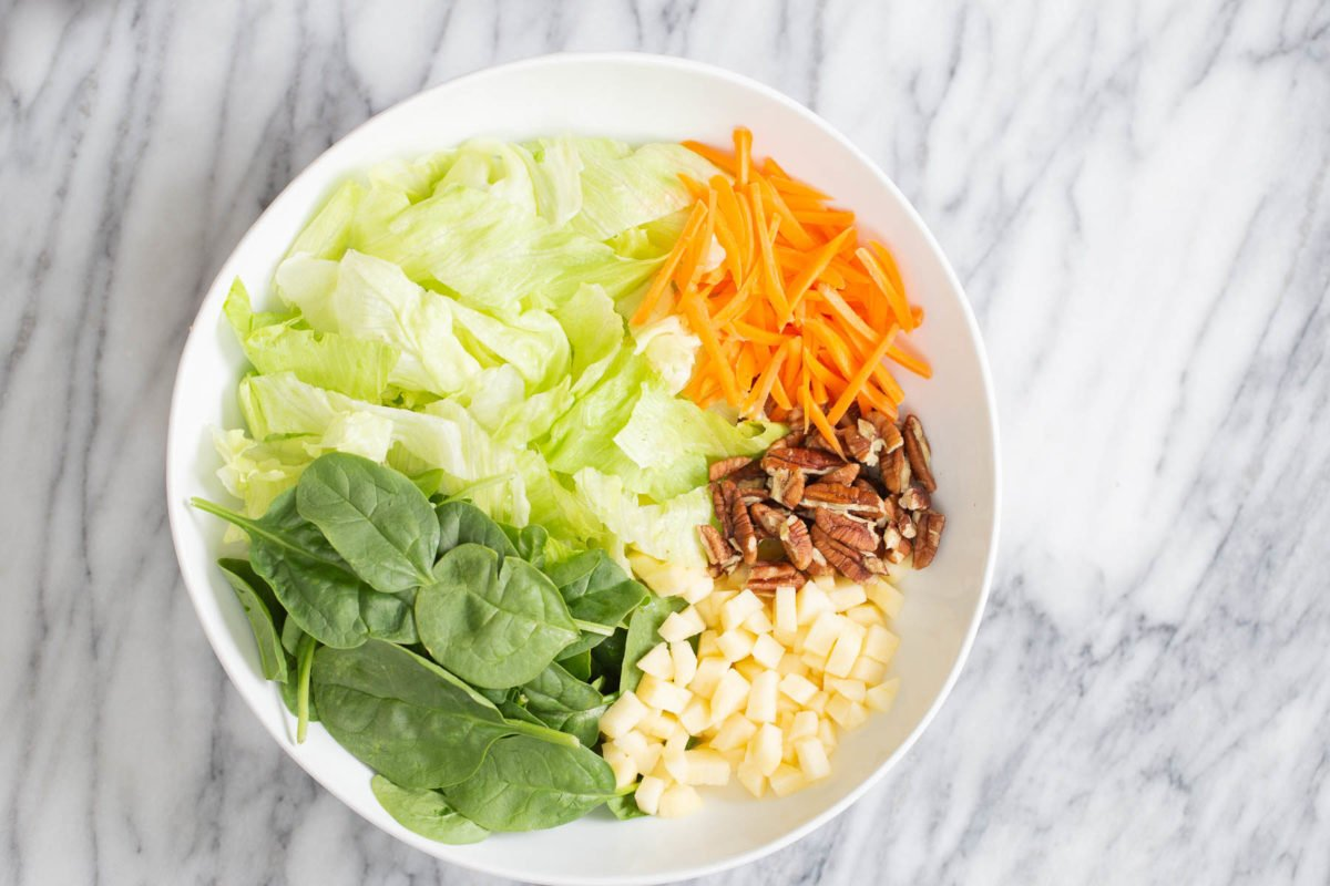 overhead shot of a salad bowl with spinach and iceberg lettuce, carrots, pecans and apples