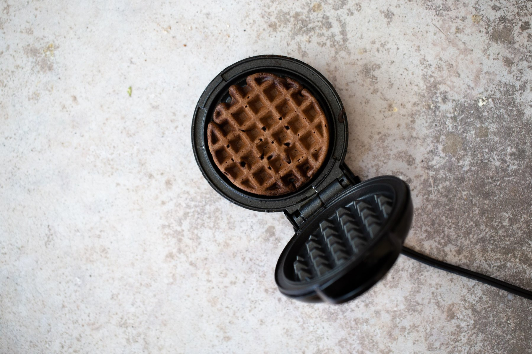 overhead shot of a waffle iron with a buckwheat waffle in it
