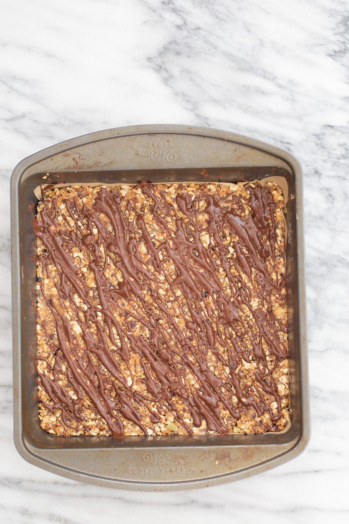 foto aérea de uma caçarola com barras de tâmaras de caramelo de coco vegano regadas com chocolate derretido
