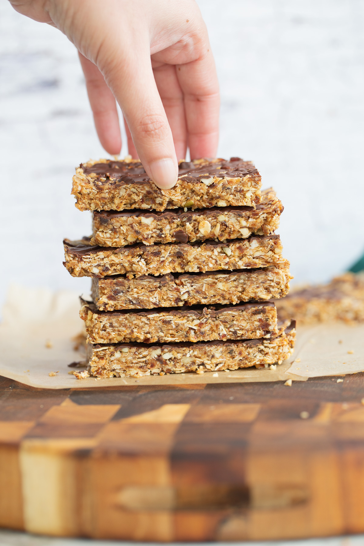 a hand reaching for a vegan date bar on top of a stack of vegan snack bars