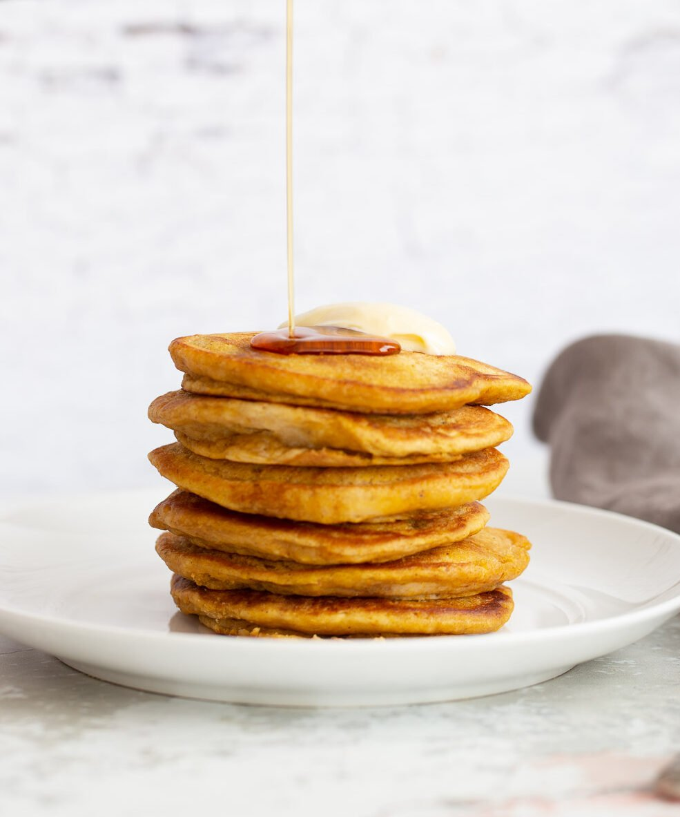 a stack of vegan pumpkin pancakes being drizzled with maple syrup