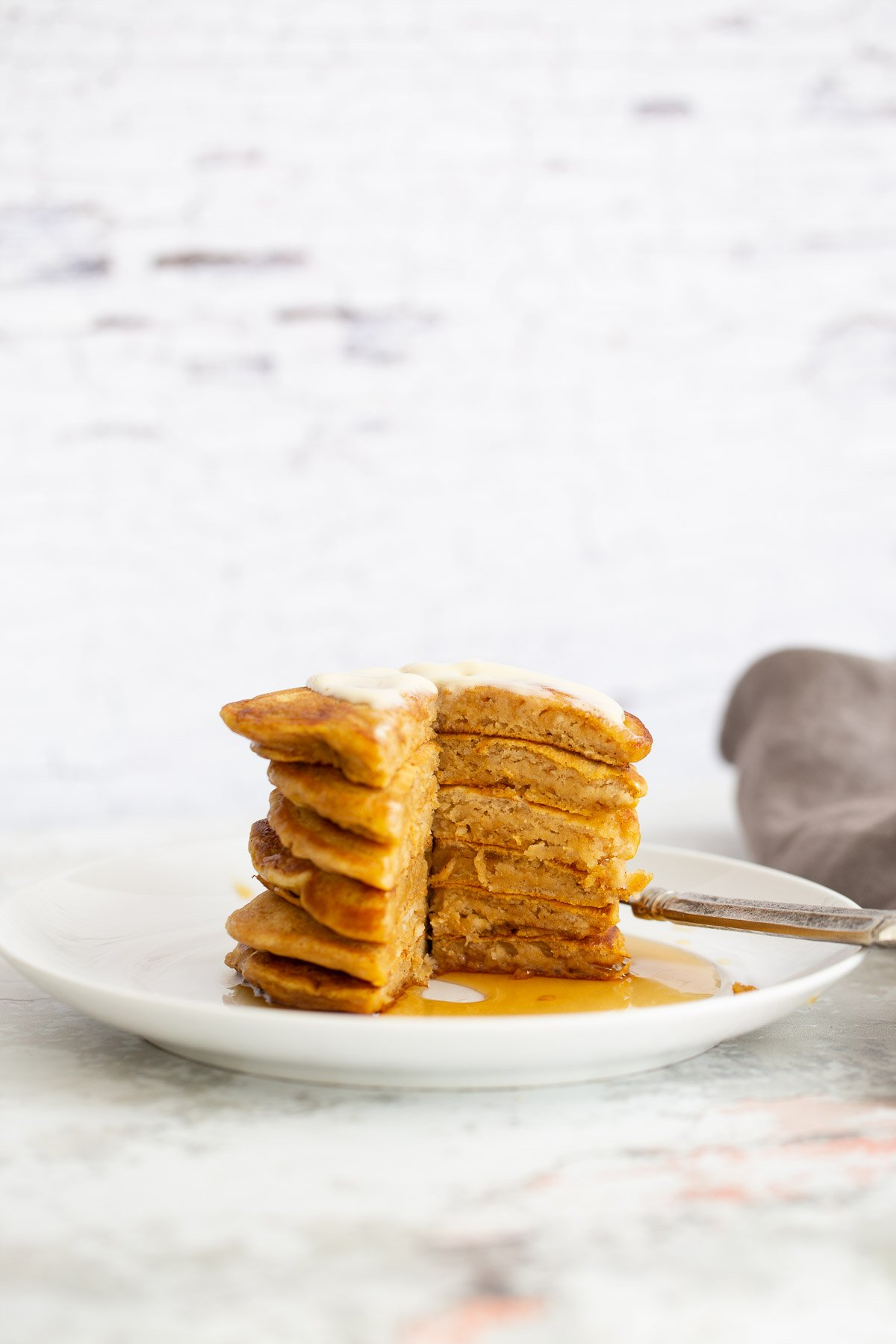 a stack of vegan pumpkin pie pancakes with one wedge cut out