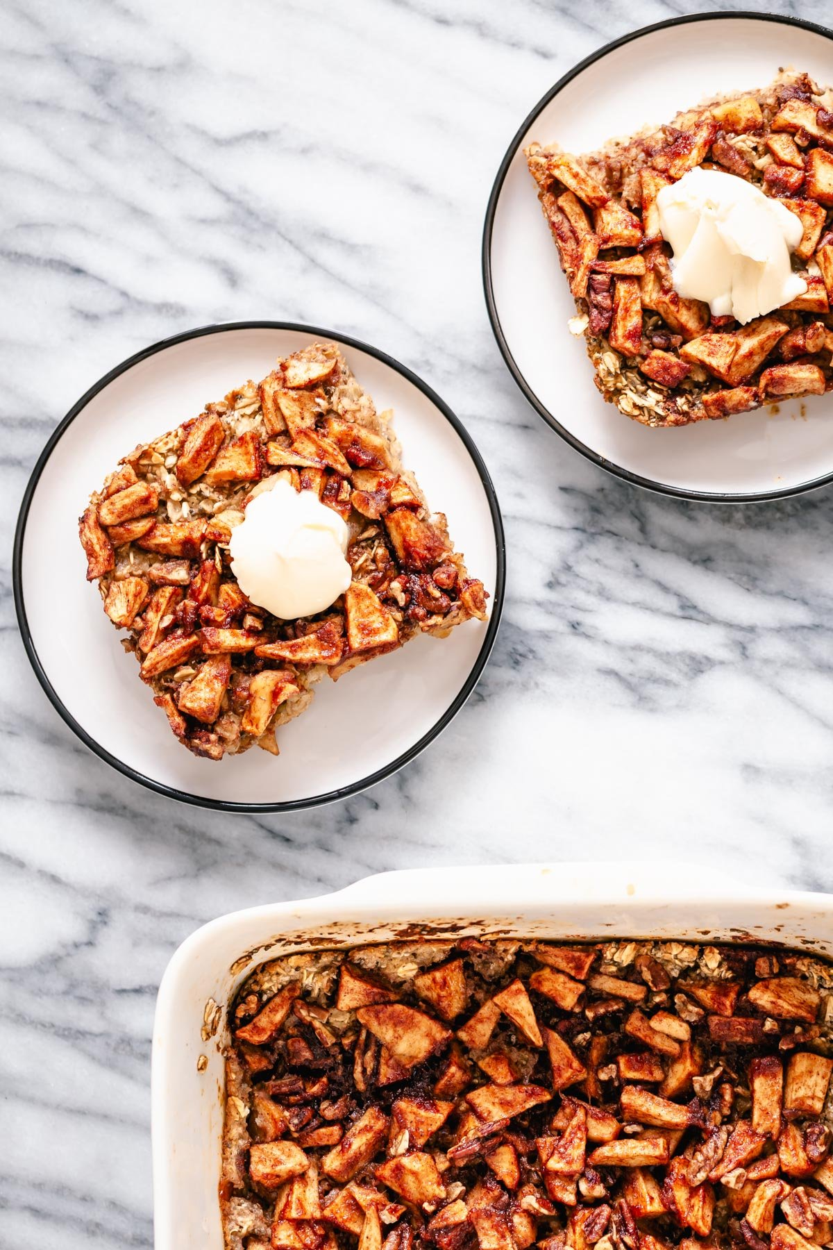 two squared of apple pie baked oatmeal served on cake plates