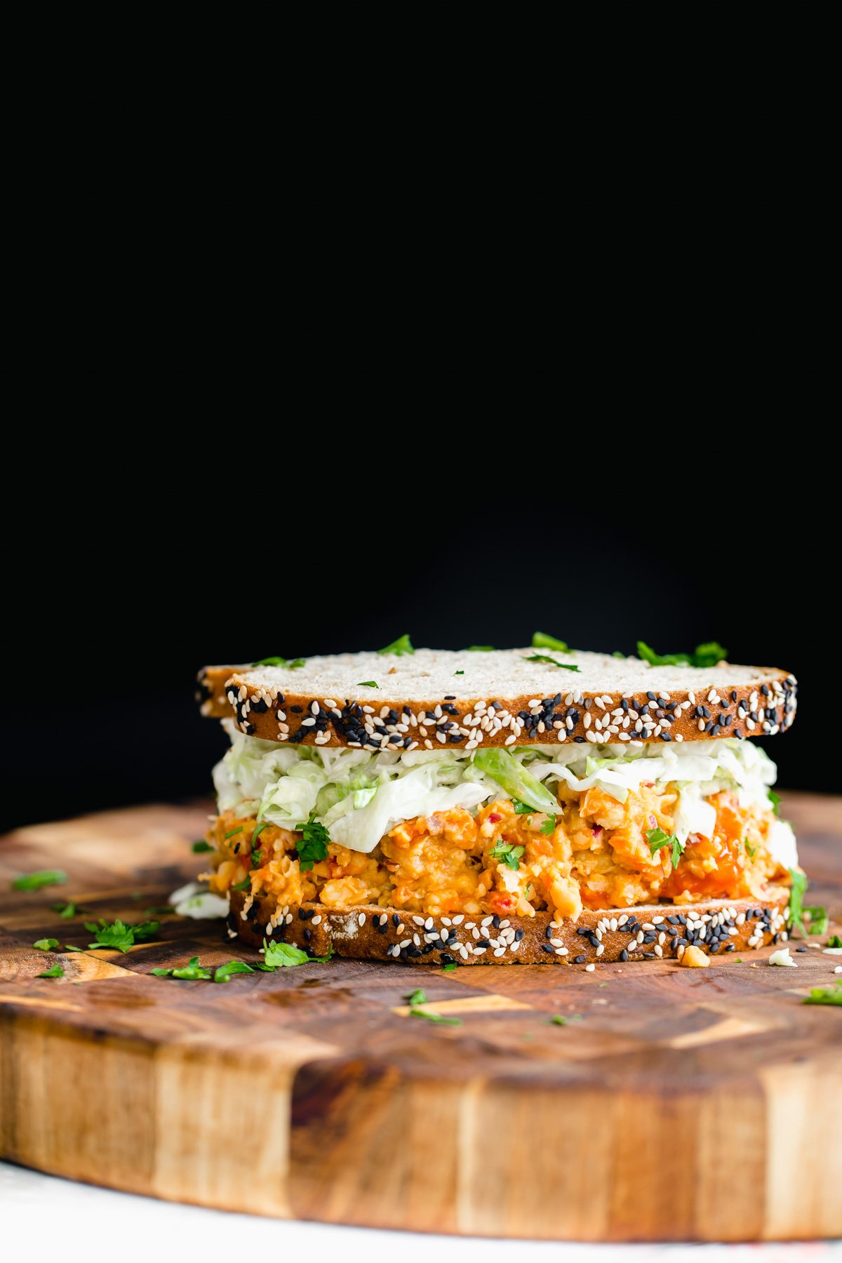 side view of vegan buffalo chickpea salad sandwich on a wooden board