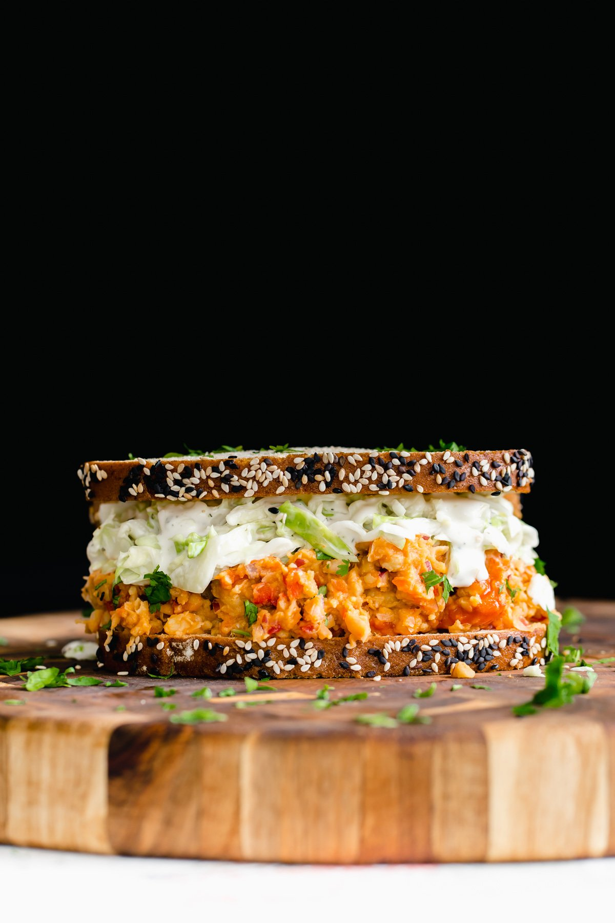 side view of a vegan lunch sandwich with buffalo chickpea salad and slaw