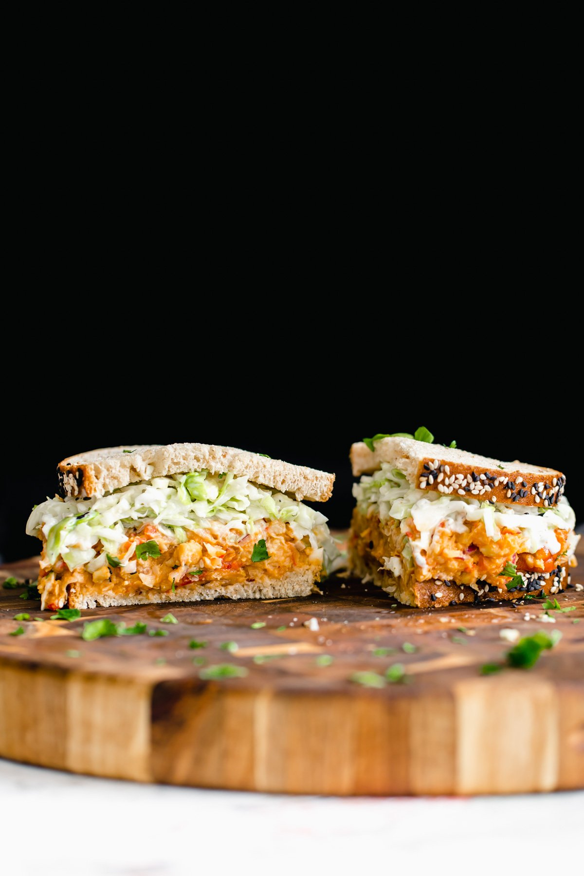 a halved chickpea salad sandwich on a wooden board