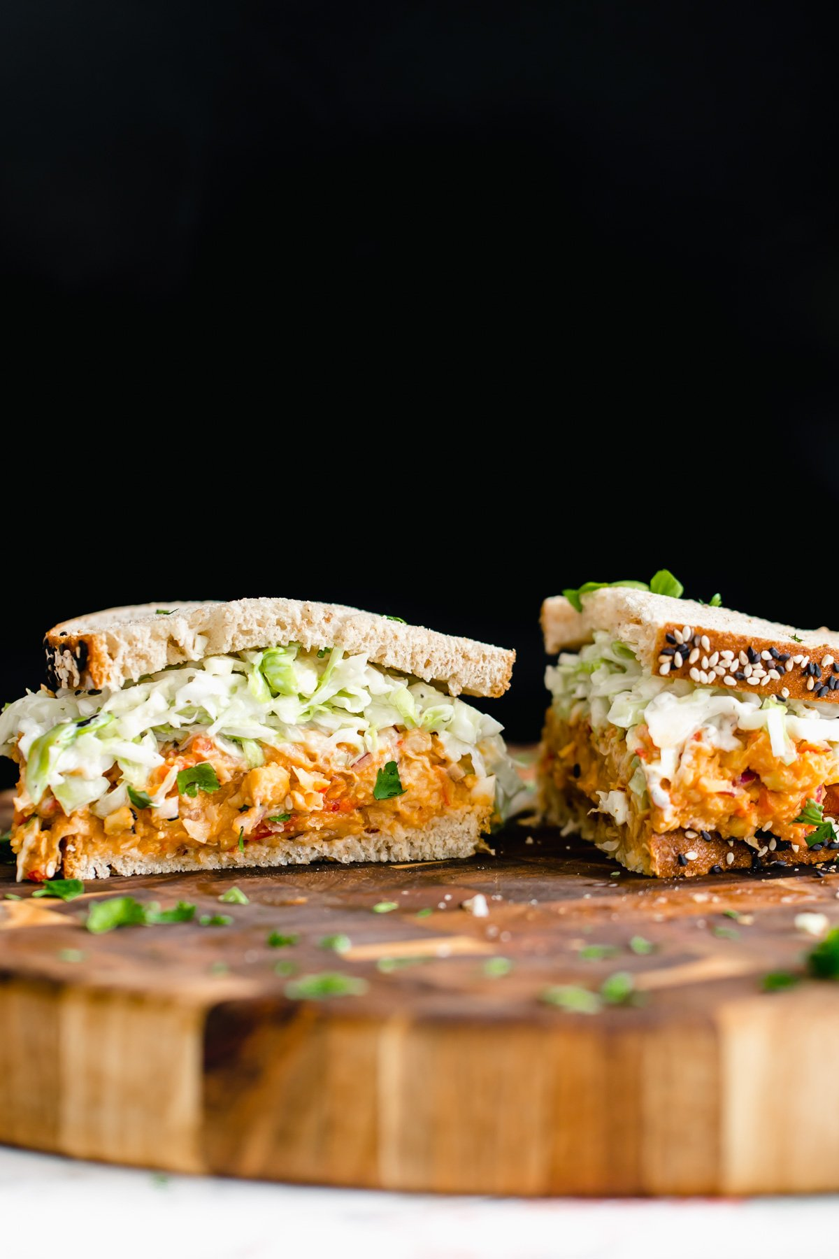 a halved buffalo chickpea salad sandwich with slaw on a wooden chopping board
