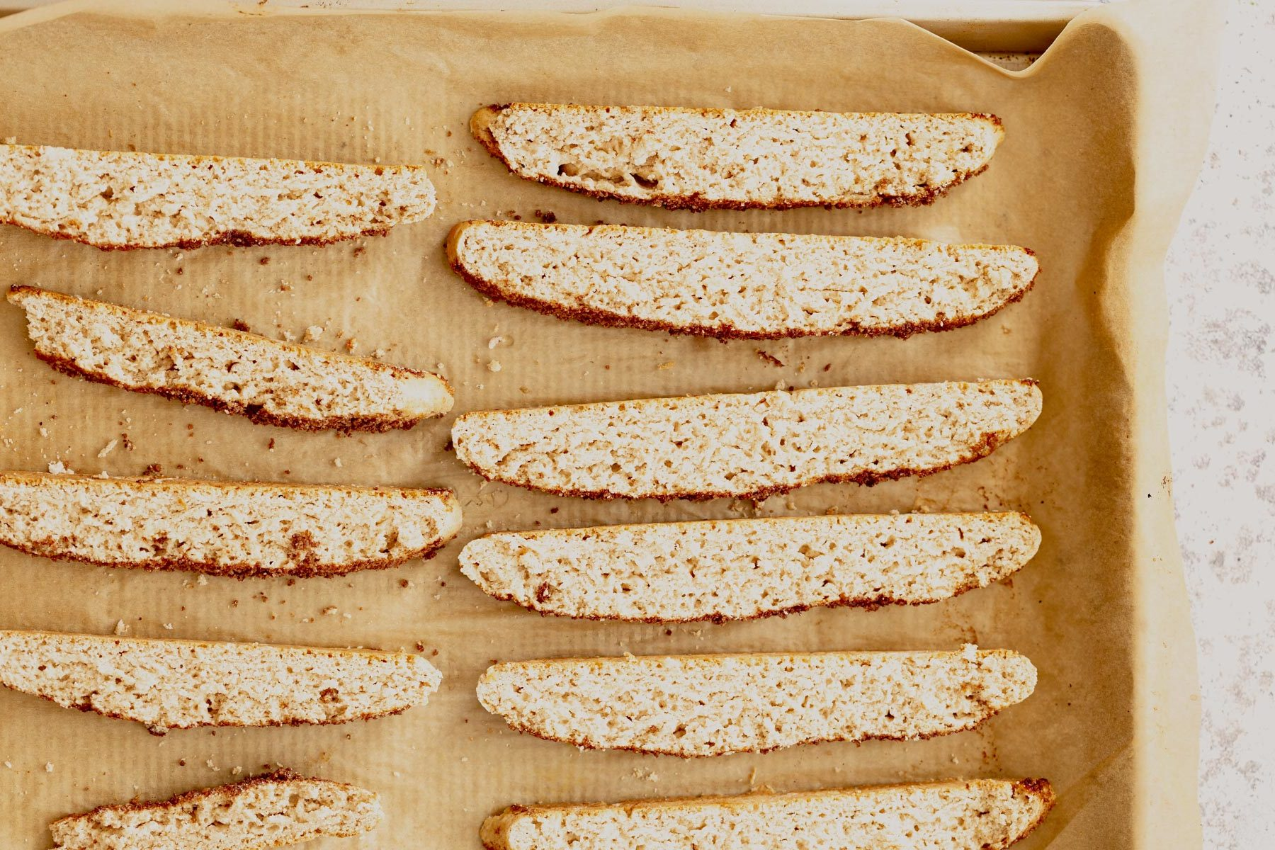 vegan cinnamon sugar biscotti on a parchment paper lined baking sheet