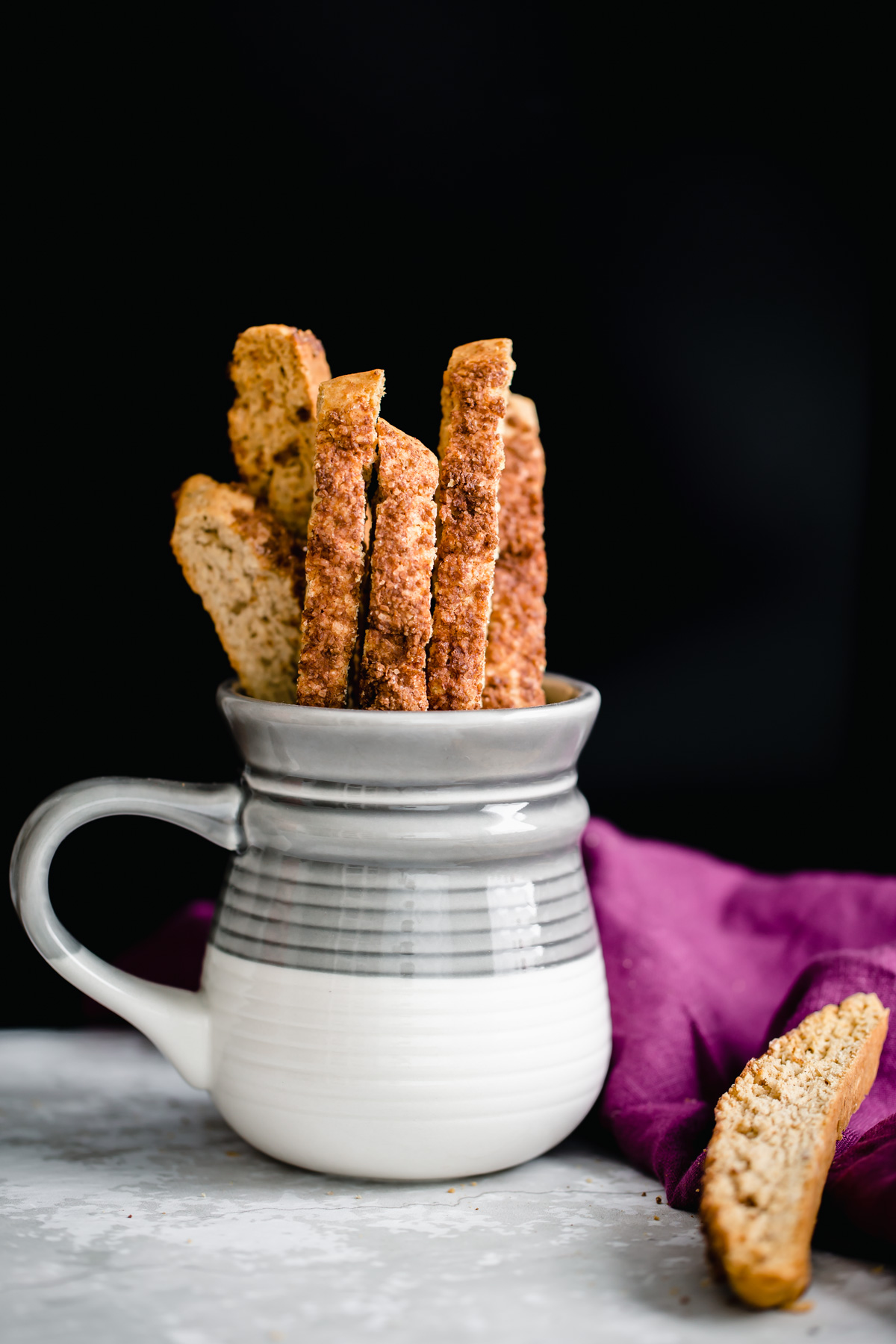 homemade vegan churro biscotti peaking out of a grey and white coffee mug