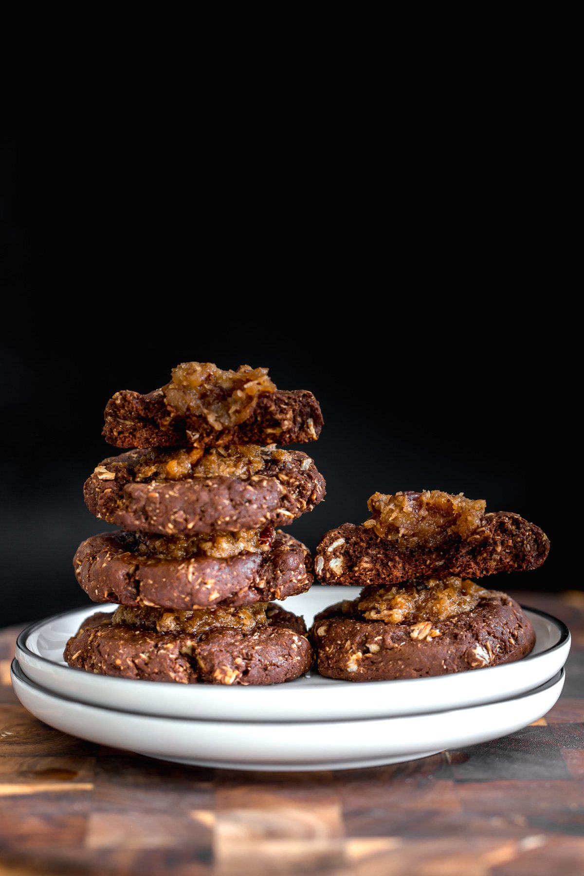 a plate with stacked homemade German Chocolate thumbprint Cookies against black background