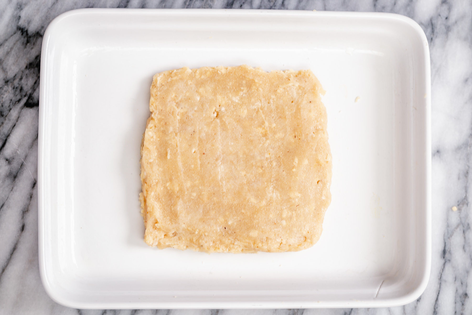 rasmalai cake batter being shaped to a square in a pan