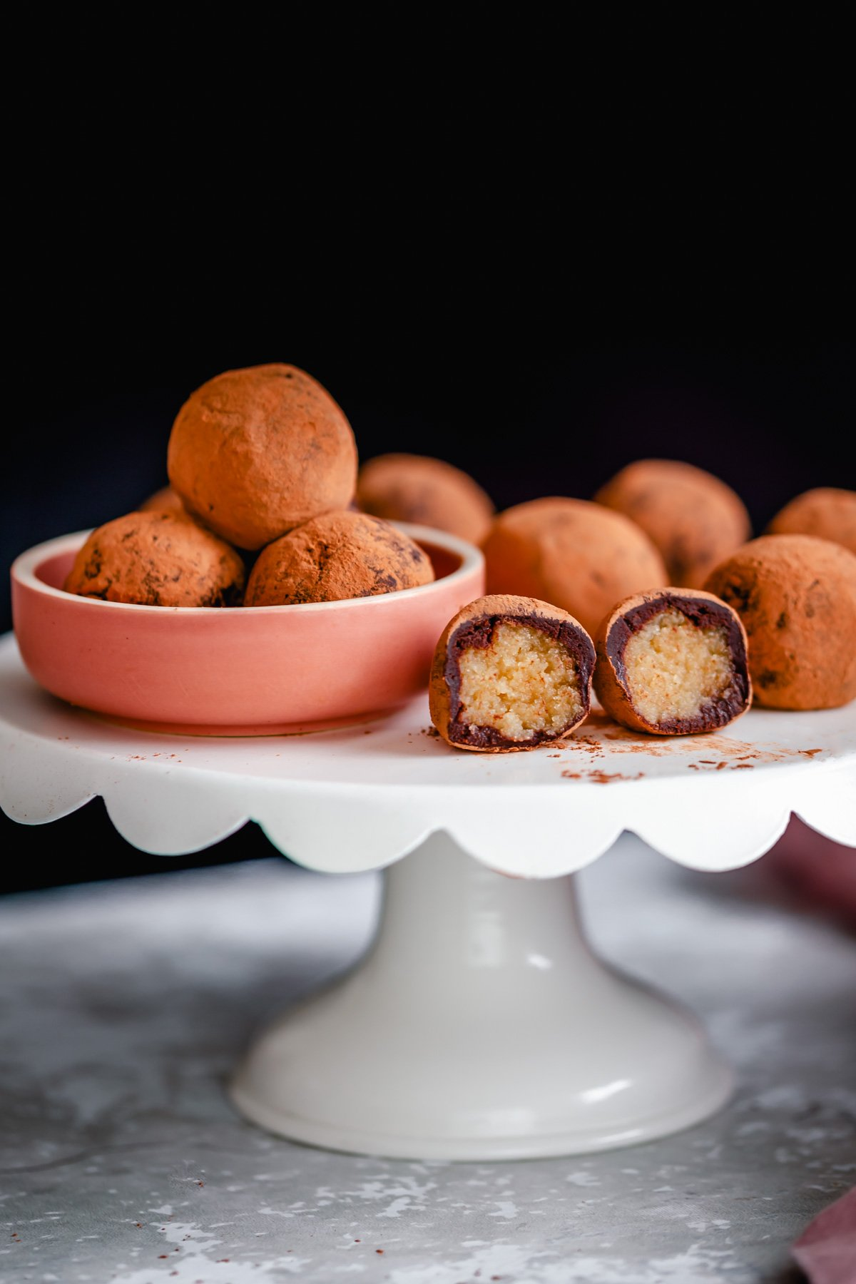 vegan tiramisu truffles on a cake stand with one truffle cut open