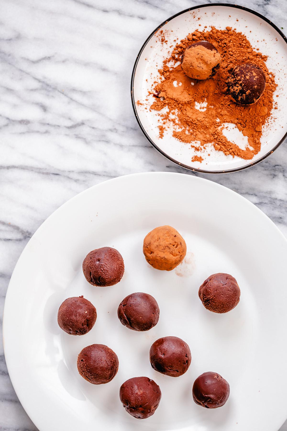 vegan tiramisu truffles being rolled in cocoa powder
