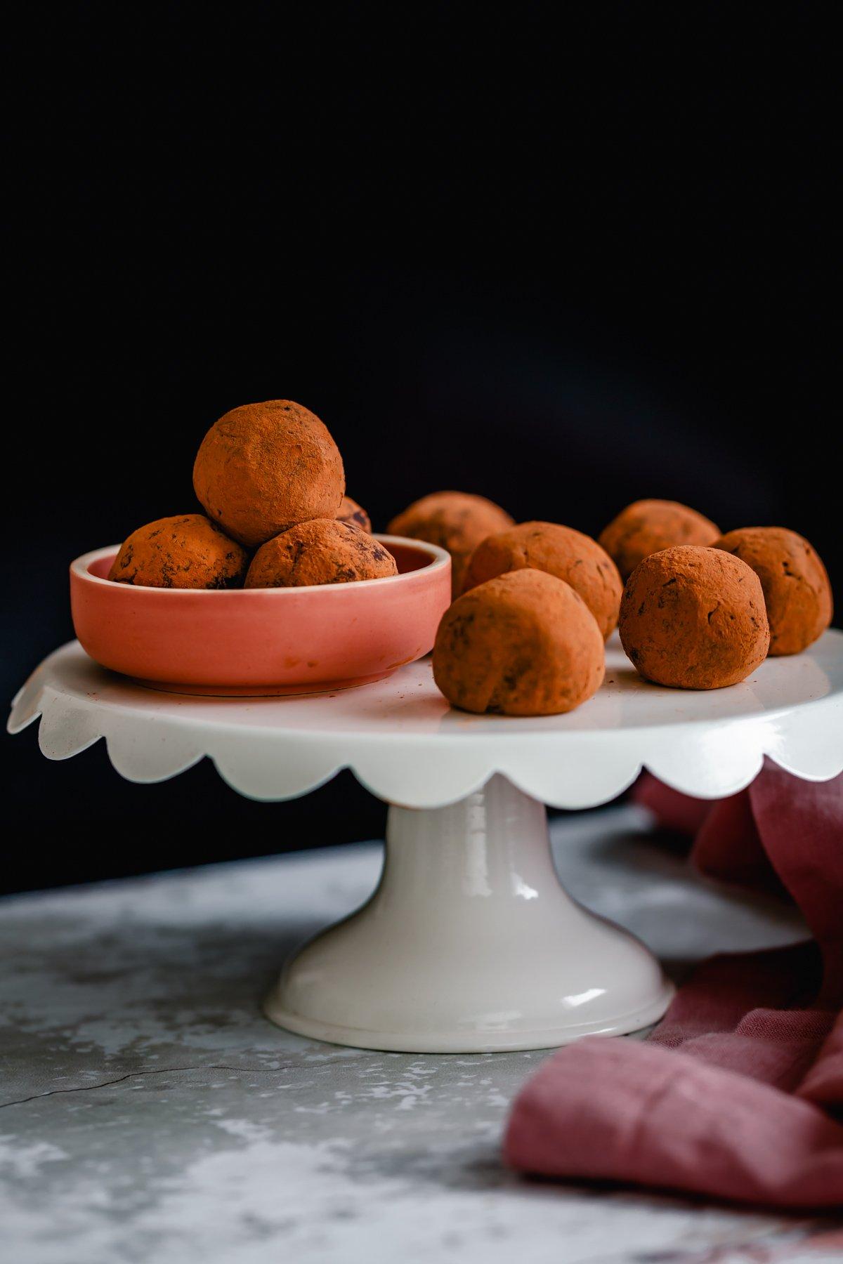 a cake stand with cocoa-dusted vegan Tiramisu truffles made with vegan cream cheese