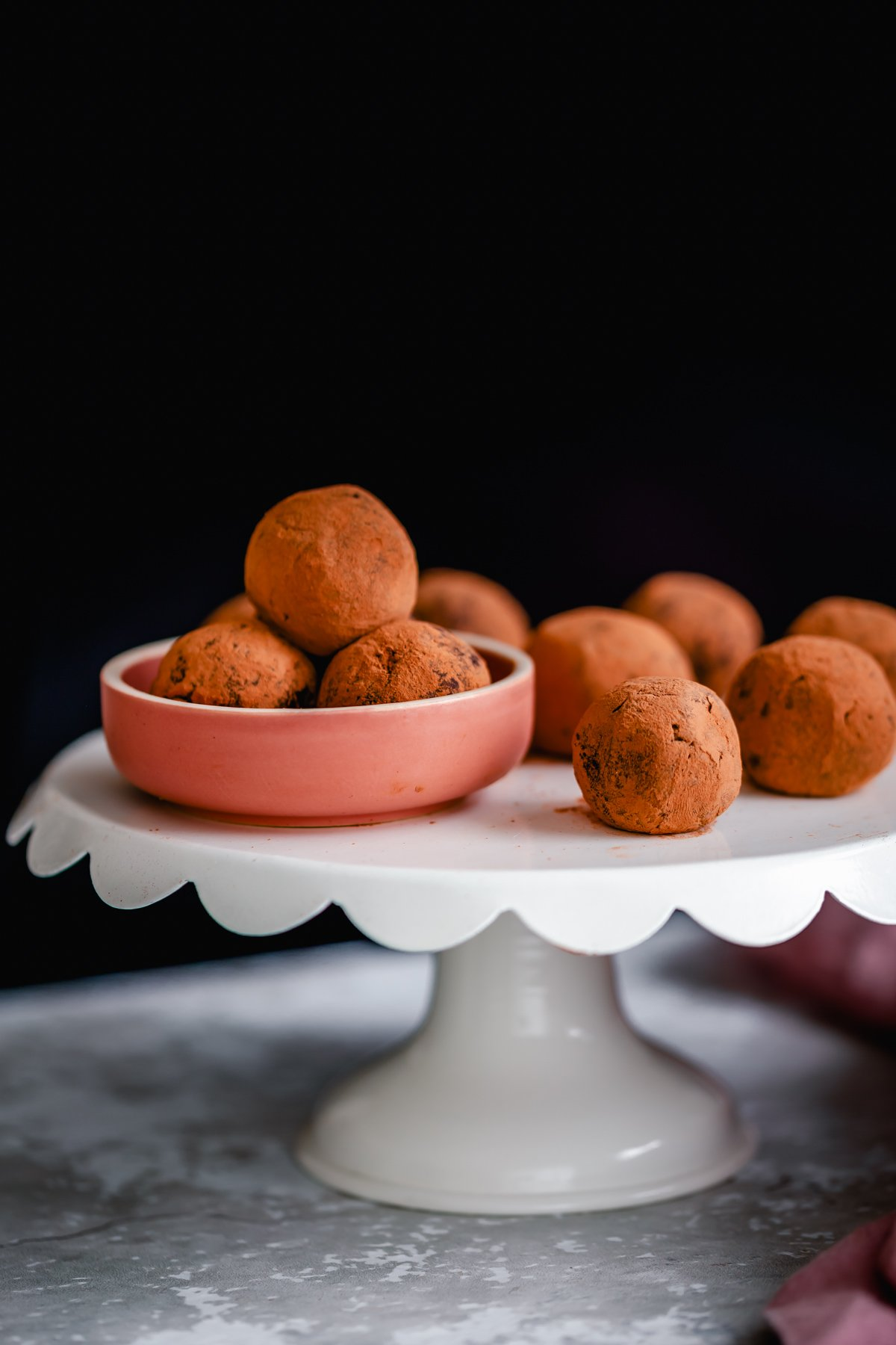 vegan tiramisu truffles rolled in cocoa powder presented on a cake stand