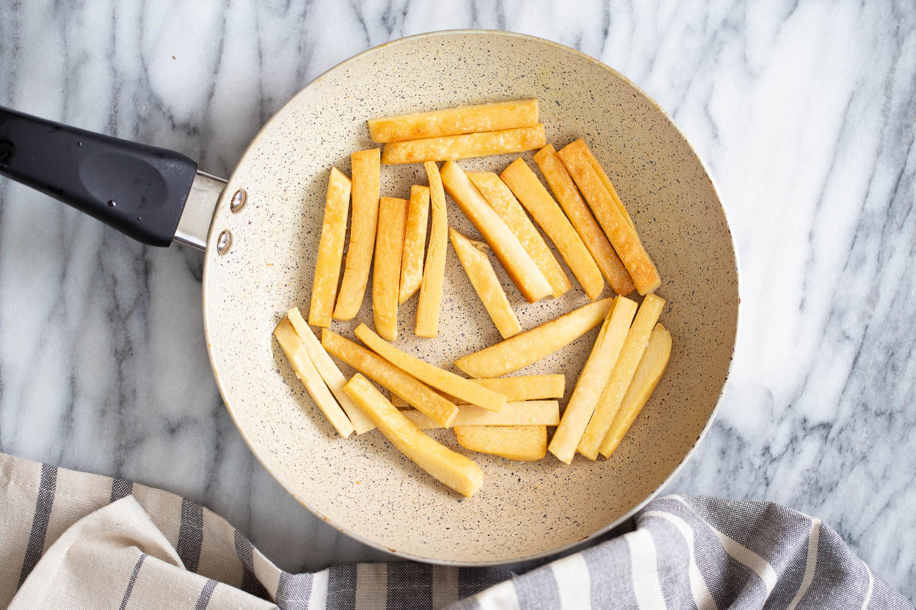 chickpea flour fries being pan-fried in a skillet