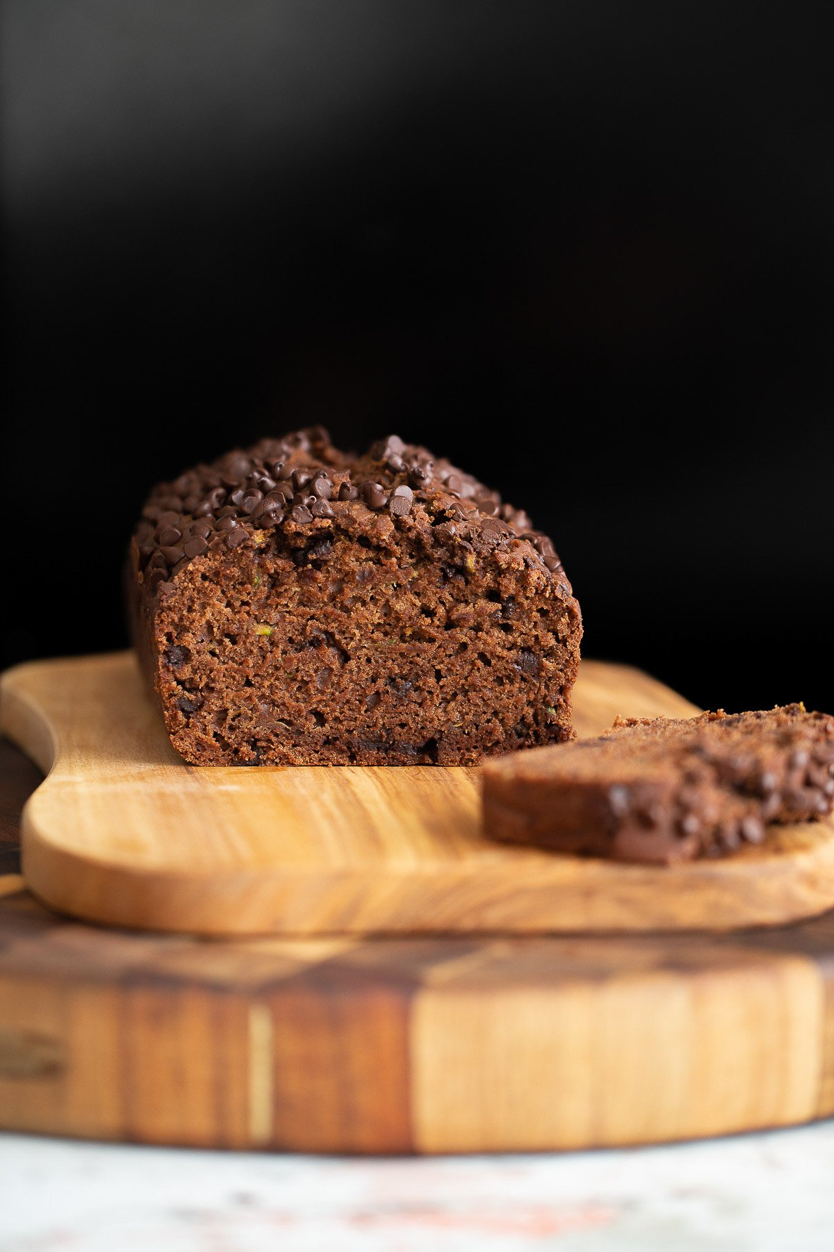 a sliced loaf of chocolate zucchini bread on a wooden chopping board